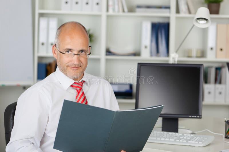 Säkert moget affärsmanWith File At skrivbord arkivfoton