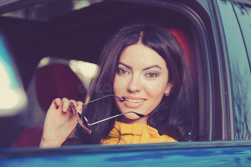 Säkert och härligt Attraktiv kvinna i gul klänning i hennes nya moderna bil royaltyfria bilder