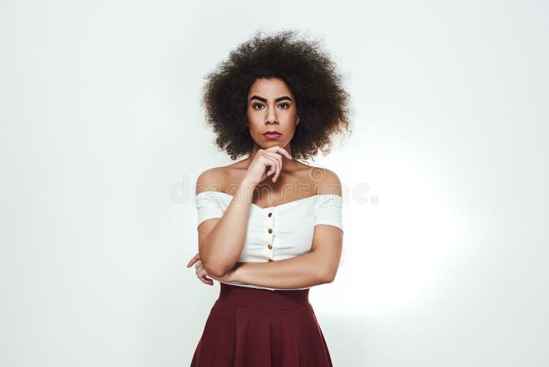Säkert och härligt Den unga afro amerikanska kvinnan med lockigt hår rymmer handen på hakan och ser kamerastund royaltyfri fotografi