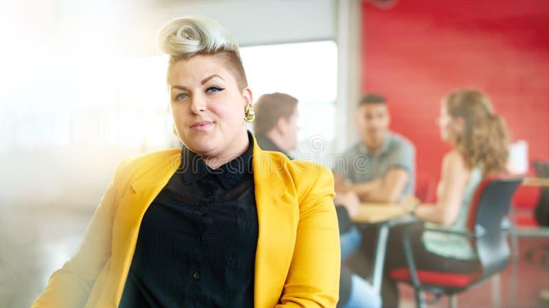 Säkert och lättretligt kvinnligt märkes- arbete på en digital minnestavla i rött idérikt kontorsutrymme royaltyfri foto