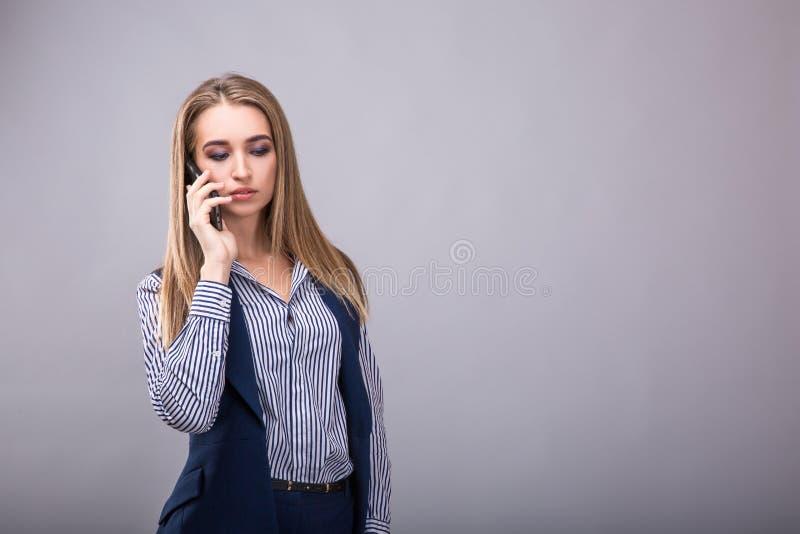 Säkert samtal Härlig ung affärskvinna som talar på mobiltelefonen, medan stå mot grå bakgrund royaltyfri bild