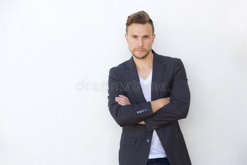 Säkert ungt anseende för affärsman mot den vita väggen royaltyfria foton