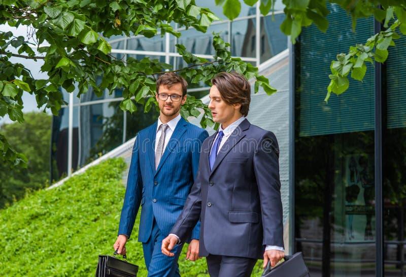 Säkra affärsmän som framme talar av modern kontorsbyggnad Affärsman och hans kollega Packa ihop och finansiellt royaltyfri fotografi