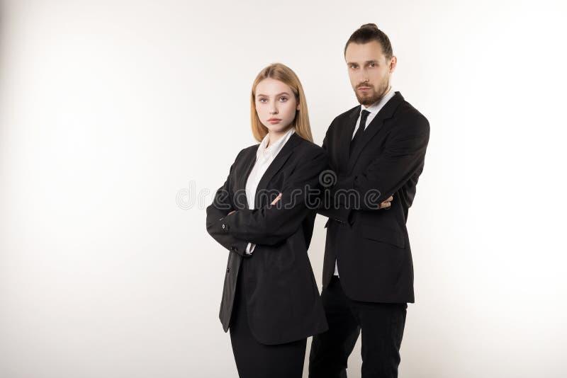 Säkra allvarliga businesspeople som poserar i svarta dräkter och att stå med crosed händer som ser kameran arkivbilder