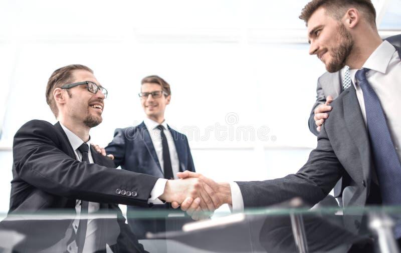 Säkra handskakningaffärspartners på skrivbordet arkivfoton