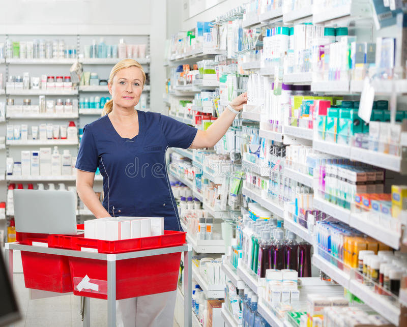 Säkra kemistArranging Medicines In hyllor royaltyfri bild
