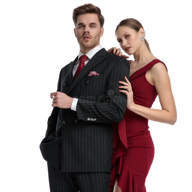 Säkra par som stirrar på kameran och är klätt elegant royaltyfri bild