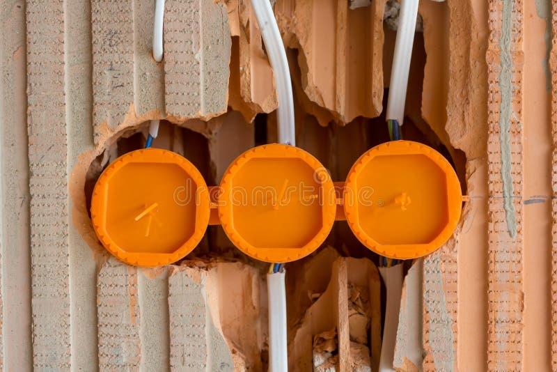 Säkrad elektrisk hålighet mot att rappa i vägg för röd tegelsten i hus under konstruktion royaltyfri bild