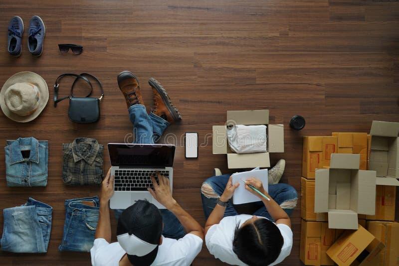 Sälja den online-för idéer begrepp, funktionsdugliga bärbar datordatoren för man och kvinnaanteckningsboken arkivfoton