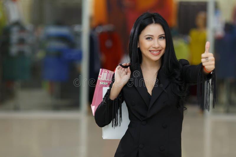 Sälja i minut, gest- och försäljningsbegreppet - le kvinnan med många shoppingpåsar som visar upp tummar arkivbild