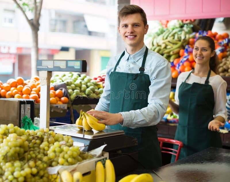 Säljare med bananer på marknaden arkivfoton