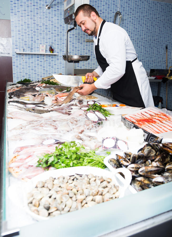 Säljare med knivsnittfisken royaltyfria foton