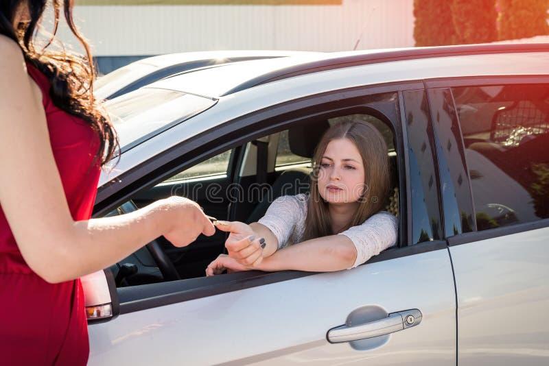 Säljare som ger tangent från bilen till chauffören arkivfoton