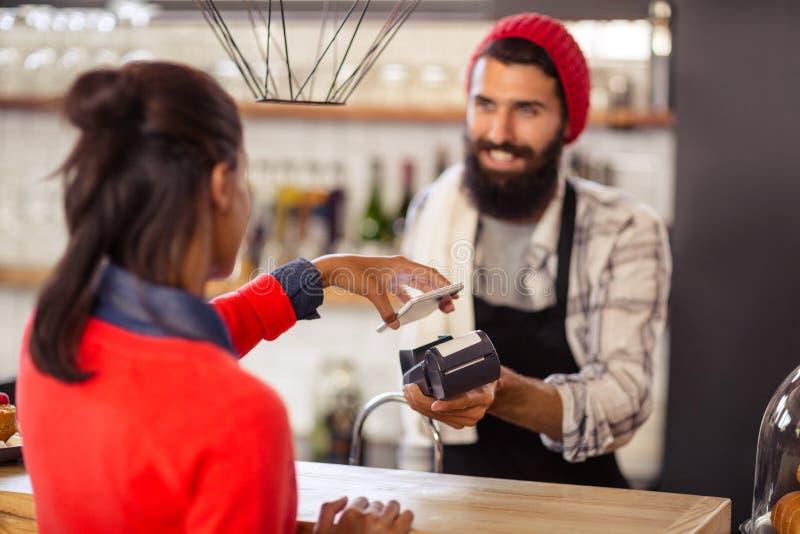 Säljare som tar betalning med kontokortavläsaren och smartphonen fotografering för bildbyråer