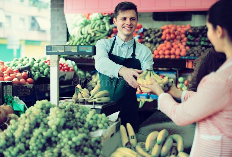 Säljare som väger bananer arkivbilder