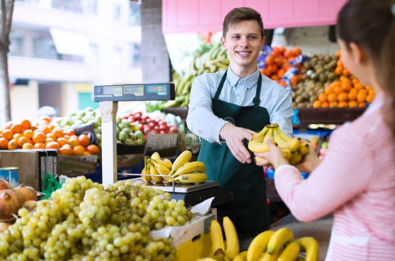 Säljare som väger bananer royaltyfria foton
