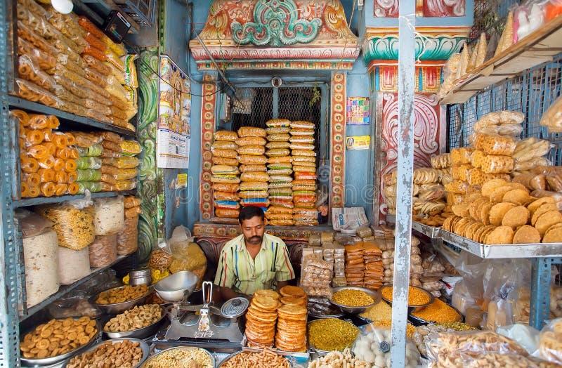 Säljaren av sötsaker väntar på köpare i ett färgrikt shoppar med kex och mellanmål fotografering för bildbyråer
