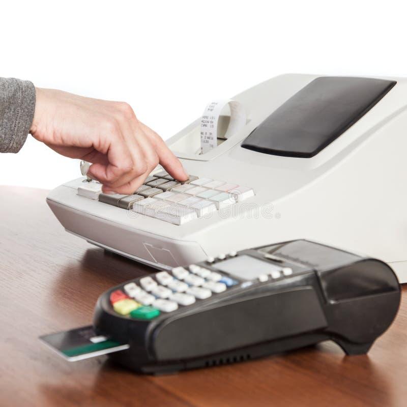 Säljaren gör beräkningen och tar betalning vid en kassareg arkivbilder