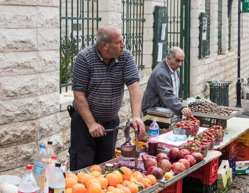 Säljaren gör nytt sammanpressad granatäpplefruktsaft i den östliga basaren i den gamla staden av Nazareth i Israel royaltyfria bilder