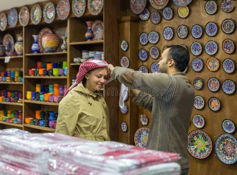 Säljaren hjälper turisten till pålagt hennes huvud en nationell arabisk huvudbonad - keffiyeh i en vägren shoppar nära den Kerak  royaltyfria foton