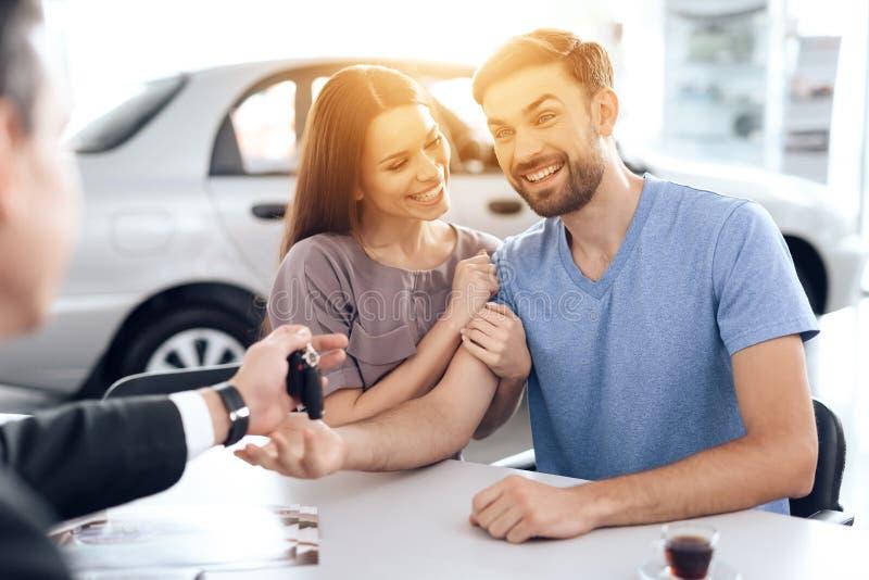 Säljaren i bilvisningslokalen ger biltangenterna till köparen fotografering för bildbyråer