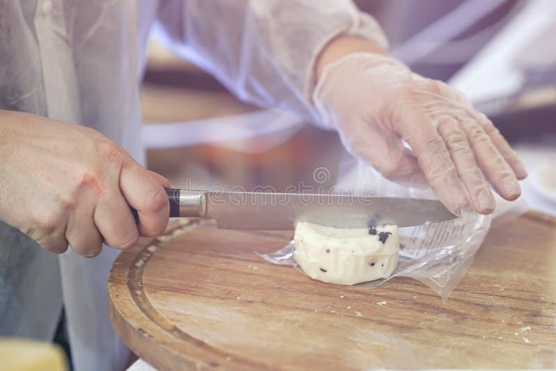 Säljaren klipper, säljer ost med tryffeln, snittosthuvud på trämarknadsbräde Händer med knivnärbild gastronomiskt arkivbilder