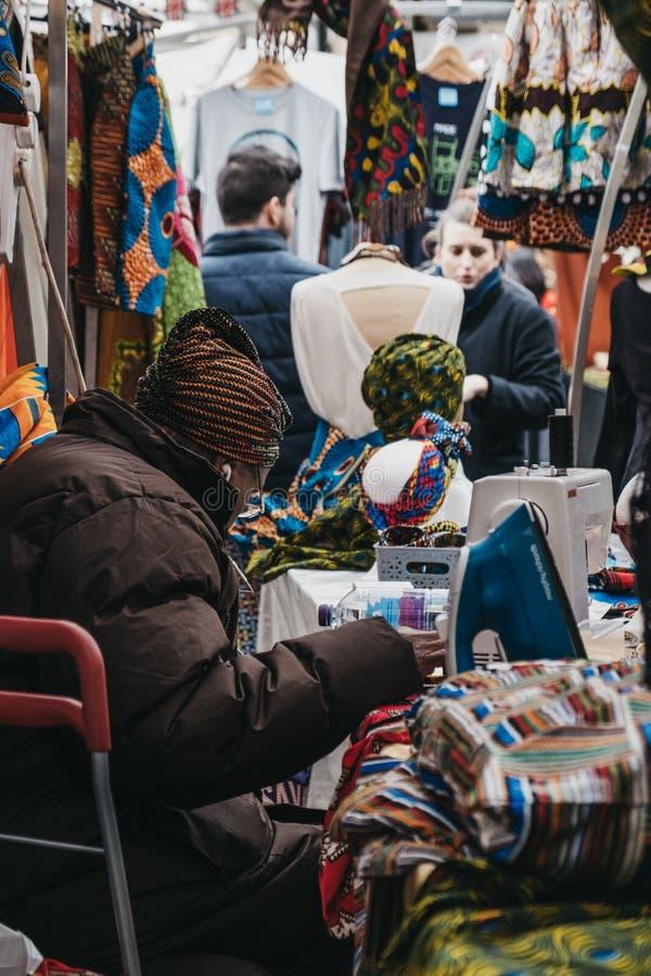 Säljaren som syr på ett tyg, stannar inom den Greenwich marknaden, London, UK arkivfoto