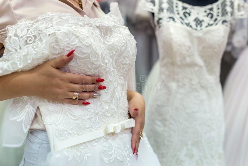 Säljares händer med bröllopsklänningen, slut upp royaltyfri bild