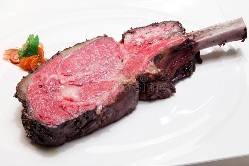 Sällsynt för galler för läggnötköttbiff medelmed tomaten på den vita maträtten royaltyfri bild