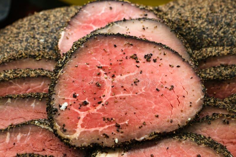Sällsynt lagat mat pepprat öga av runt steknötkött som skivas i en hög jpg arkivbild