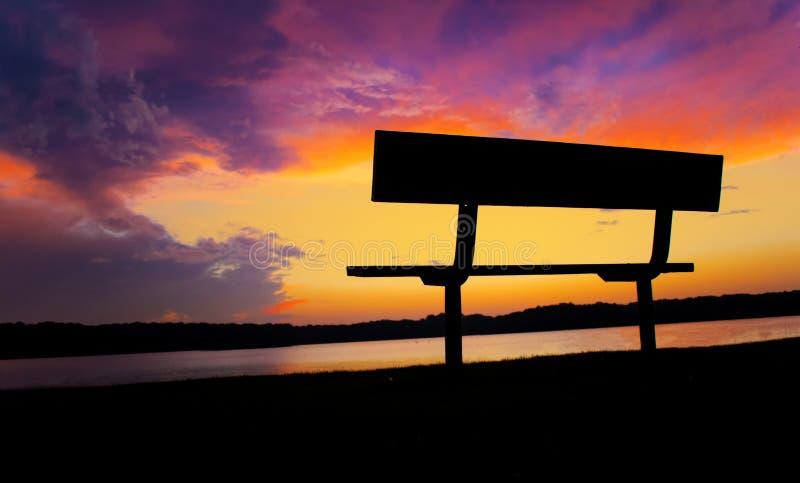 Sällsynta spektakulära molnbildande under solnedgång över lugna sjövatten och koppla avbänk royaltyfri bild
