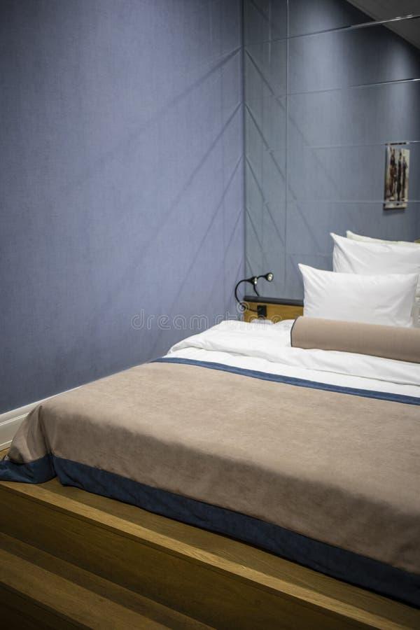 Säng för hotellkonungformat på en blå vägg och en stor spegel royaltyfri foto