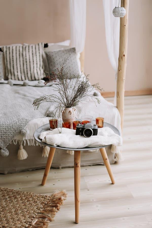 Säng med kuddar, filten och en nattduksbord med den retro kameran och stearinljus Exotisk sovruminre, scandinavian stil fotografering för bildbyråer