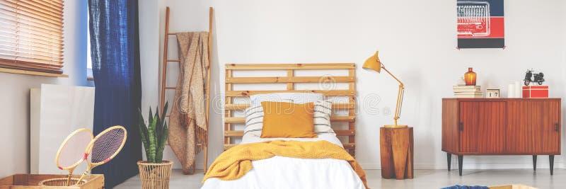 Säng med träbedhead, vita ark, ockrakudden och den gula rät maskafilten royaltyfri fotografi