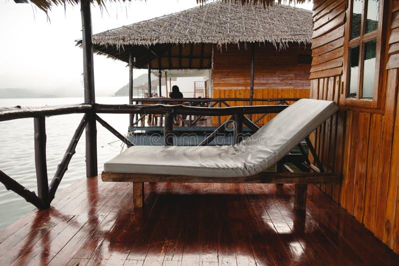Säng som förläggas på strandträbalkong, har annat trähus royaltyfri foto