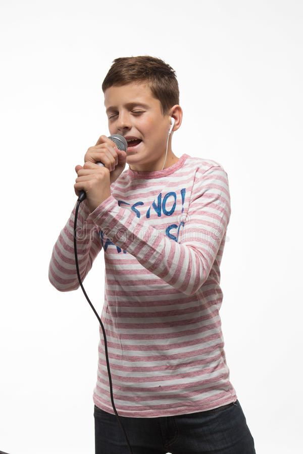 Sänger Brunettejunge in einem rosa Pullover mit einem Mikrofon und Kopfhörern lizenzfreies stockfoto