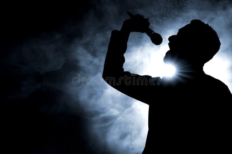 Sänger-Gesangschattenbild auf dunklem Hintergrund lizenzfreie stockfotos