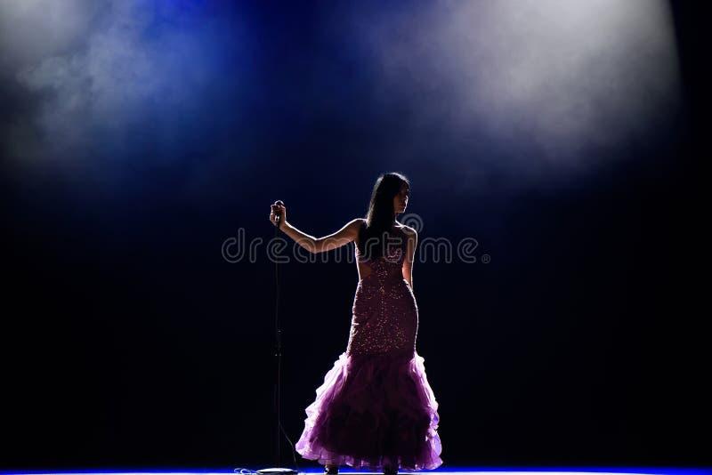 Sängerin auf dem Stadium, das ein Mikrofon hält lizenzfreies stockfoto