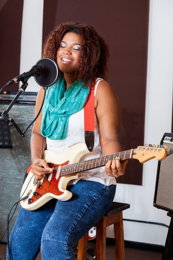Sängerin With Eyes Closed, das herein Gitarre spielt stockbilder