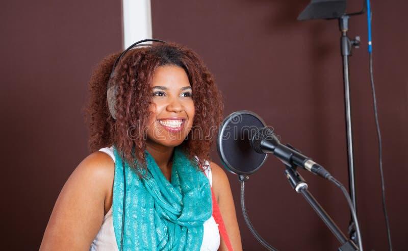 Sängerin Smiling While Performing im Studio lizenzfreie stockfotografie