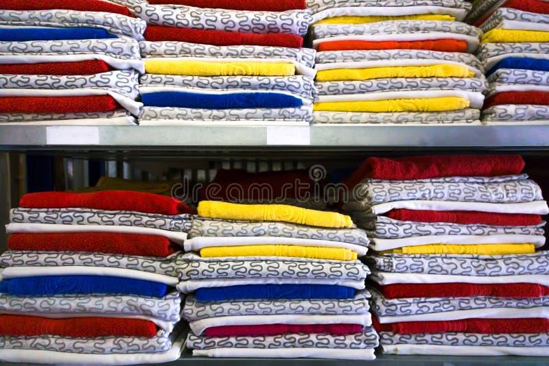 Sängkläder är i garderoben på hyllan Handdukar vek i en rulle På hängare som hänger damer och mäns kläder arkivbilder