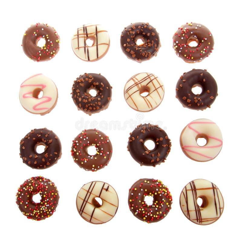 Sänka den sena miniatyrgodisen täckte donuts som isoleras på vit bakgrund royaltyfri foto
