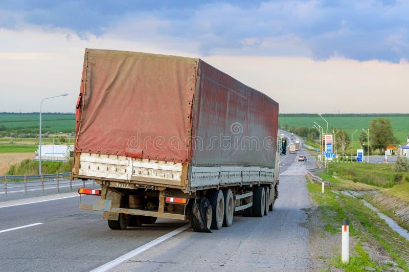 Sänka ut och för lastbilbristningen för den skadade person som drar en skottkärra halva gummihjul vid huvudväg s fotografering för bildbyråer