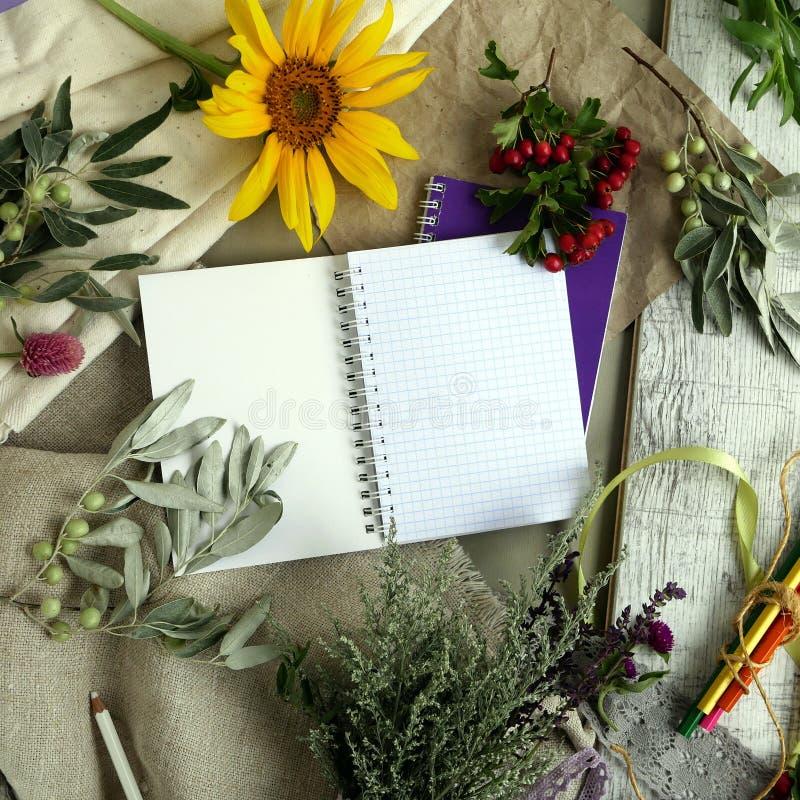 Säsongsbetonad dekorativ sammansättning av blommor, bär, konst och prästerliga material, hjärtor som göras av filt på en bakgrund arkivfoto