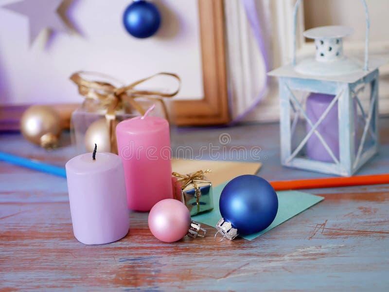 Säsongsbetonad festlig inre sammansättning av stearinljus, juldekor, trätappningramar, dekorativa lampor, papper för anmärkningar royaltyfri fotografi