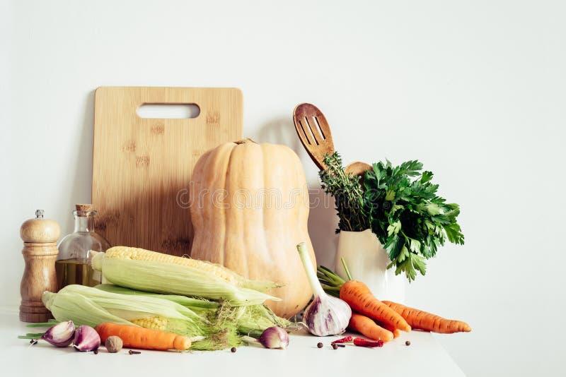 Säsongsbetonad grönsak- och köksgerådstilleben för höst på tabellväggbakgrund Tacks?gelsematbegrepp royaltyfri foto