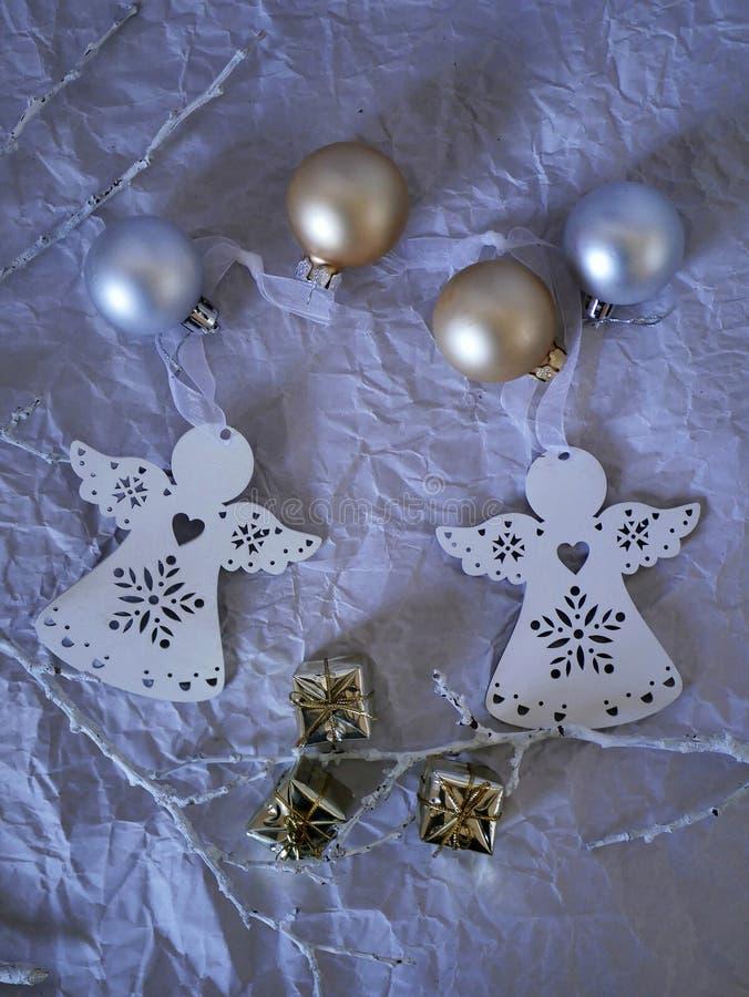Säsongsbetonad sammansättning av dekoren av två vita guld- och silverbollar för änglar för julpynt, på en bästa sikt för ljus bak fotografering för bildbyråer