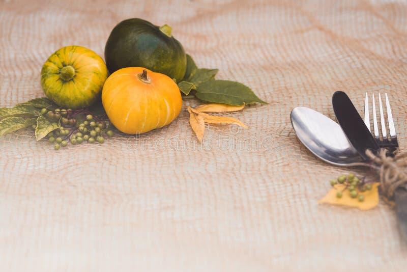 Säsongsbetonad tabellinställning med små pumpor och guling- och gräsplansidor royaltyfri bild