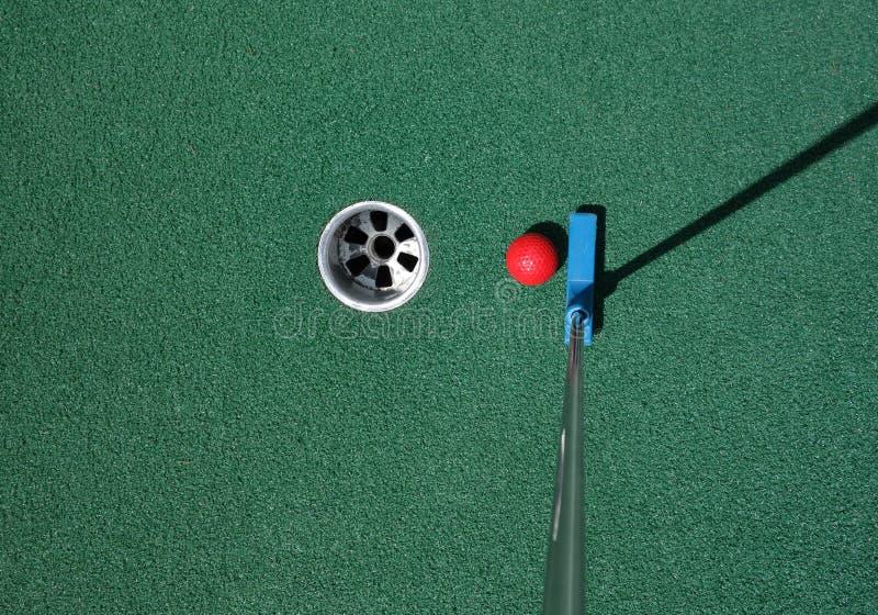 Sätta bollen på en mini- golfbana arkivbilder
