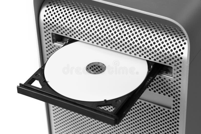 Sätta in en vit CD/DVD in i en dator royaltyfri fotografi